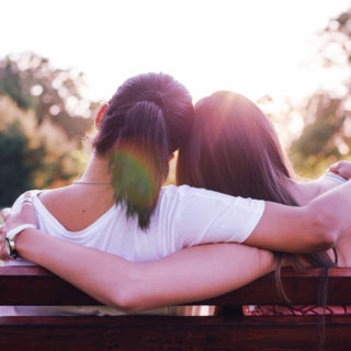 Two people embraced on a park bench.