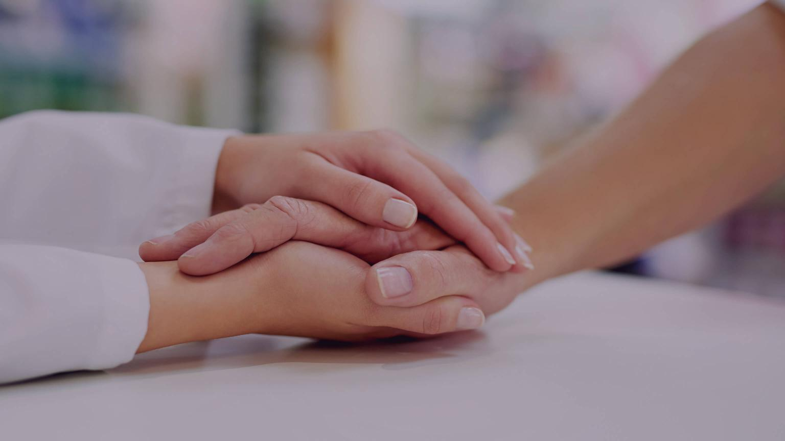 Two hands embracing across a desk